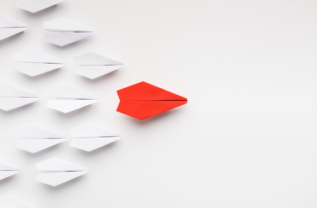 Foto de Opinion leadership concept. Red paper plane leading another ones, influencing the crowd, white background, top view with free space - Imagen libre de derechos