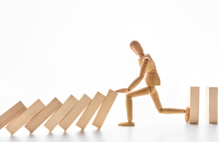 Photo pour Strength of leader. Wooden mannequin stopping domino effect on white background, free space - image libre de droit