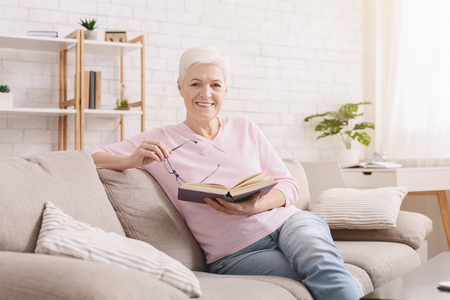 Photo for Learning foreign languages. Cheerful senior woman reading educational book at home - Royalty Free Image