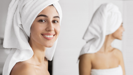 Foto de Smiling cute girl with towel on her head standing in front of mirror in bathroom, looking at camera. Pampering and beauty care concept - Imagen libre de derechos