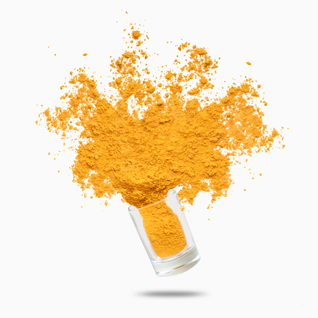 Condiment splash. Yellow turmeric powder flying, isolated on white background