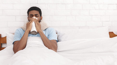 Photo pour Sick african-american guy blowing his nose into paper napkin in bed, panorama with free space - image libre de droit