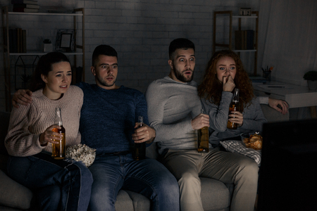 Photo pour Friends watching horror films, eating popcorn and drinking beer at home - image libre de droit
