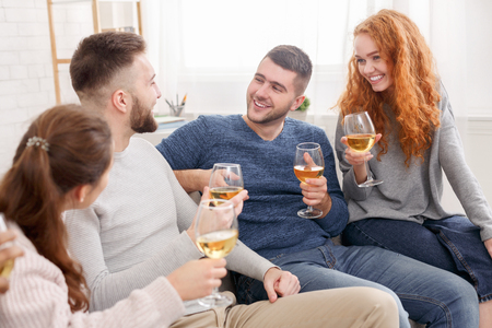 Photo pour Celebrate meeting. Friends drinking wine and talking at home - image libre de droit
