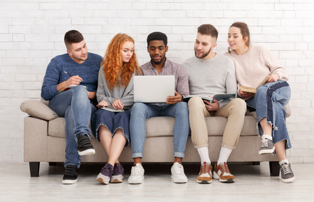 Photo pour Students preparing for exams together, sitting on sofa over white wall - image libre de droit