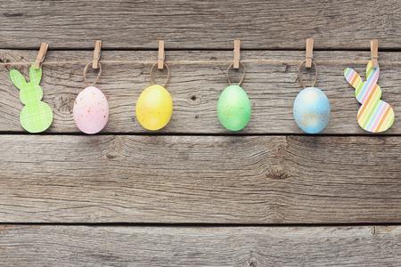 Photo pour Colourful quail eggs an paper rabbits on rope with clothes pins, copy space - image libre de droit