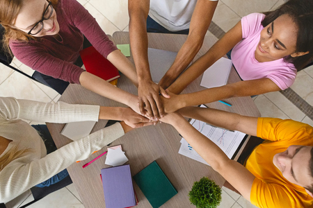 Photo pour Multiracial teenagers joining hands together in cooperation, preparing common academic project, top view - image libre de droit