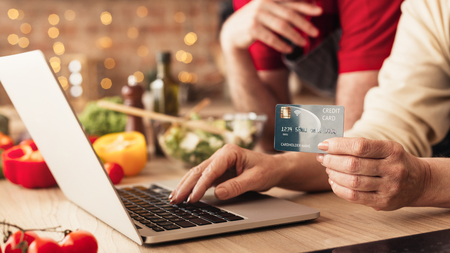 Photo pour Modern technologies in everyday life. Senior couple using laptop in kitchen for online shopping with credit card, panorama - image libre de droit