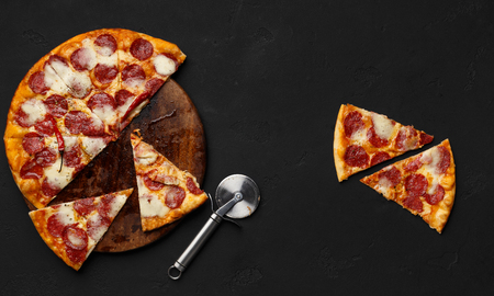 Photo pour Sliced pepperoni pizza on cutting board with cutter nearby, top view - image libre de droit