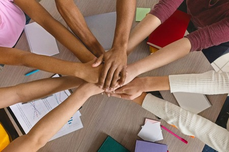 Photo pour Friendship and teamwork. International college students stacking hand together, top view - image libre de droit