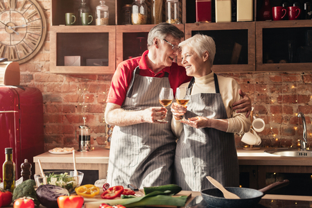 Photo pour Cheers, dear. Cheerful senior man and woman clinking with wine glasses in kitchen interior - image libre de droit