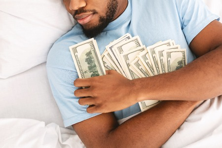 Photo pour Greedy african american guy sleeping and keeping lots of currency notes in bed, top view - image libre de droit
