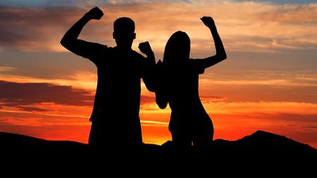 Photo pour Celebrate success. Silhouette of couple against sky at sunset - image libre de droit