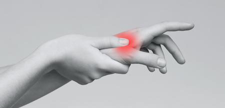 Foto de Acute pain in female palm. Woman holding hand to spot of palm-ache, panorama - Imagen libre de derechos