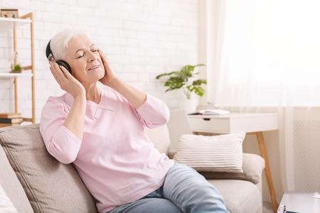 Foto de New life of favorite book. Senior woman enjoying audiobook in headphones, free space - Imagen libre de derechos