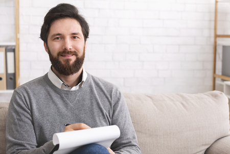 Photo pour Bearded male psychotherapist writing on clipboard and smiling at camera, sitting in office, free space - image libre de droit