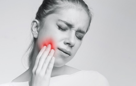 Foto de Dental problem. Young woman suffering from strong toothache, monochrome photo with red inflamed zone - Imagen libre de derechos
