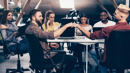 Photo pour Happy man giving fist bump to colleague, sitting at computer desk - image libre de droit