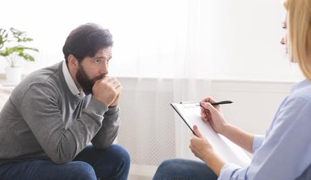 Photo pour PTSD, mental health concept. Depressed man getting psychological treatment at clinic, empty space - image libre de droit