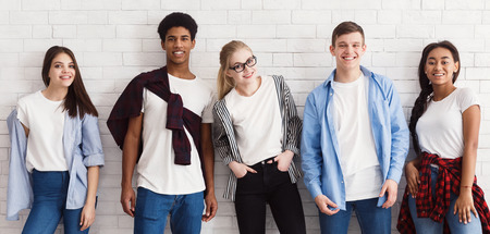 Photo pour Stylish students looking at camera and posing over white wall - image libre de droit