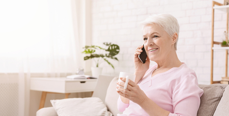 Photo pour Lovely senior lady having fun conversation with her friend or relative, drinking coffee at home, panorama, empty space - image libre de droit