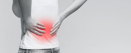Foto de Loin spasm. Young woman with hurt backbone. Spine inflammation, panorama with empty space - Imagen libre de derechos