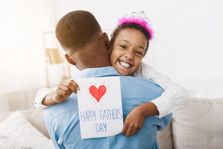 Photo pour Little girl hugging dad and giving him postcard, congratulating with fathers day - image libre de droit
