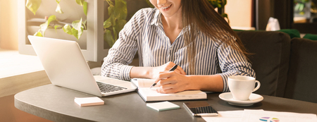 Photo pour Young woman working in cafe, typing article on laptop and taking notes, panorama with empty space - image libre de droit