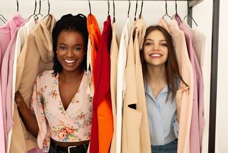 Foto per Happy girls at weekly cloth market, having fun and shopping together, looking at camera - Immagine Royalty Free