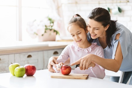 Foto de Happy family. Mom Teaching Cute Girl To Cut Apple With Knife. First lesson and healthy lifestyle concept, free space - Imagen libre de derechos