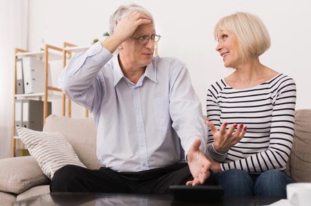 Photo pour Mature Couple Calculating Bills, Discussing Home Economics In Living Room - image libre de droit