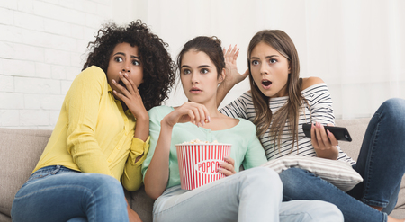Photo pour Girls watching horror movie on tv and eating popcorn at home - image libre de droit