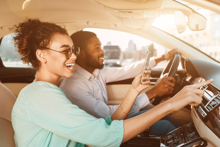Photo pour Travel Together. African-American Couple Using Navigator System, Driving Car - image libre de droit