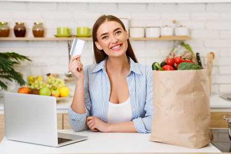 Photo pour Online Grocery Shopping. Woman With Credit Card, Laptop And Vegetables In Craft Paper Bag - image libre de droit