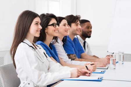 Photo for Medical Seminar. Doctors And Interns Listening To Professor In Conference Room - Royalty Free Image