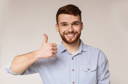 Photo pour I like it. Young man showing thumb up and smiling on camera against beige background, panorama, copy space - image libre de droit