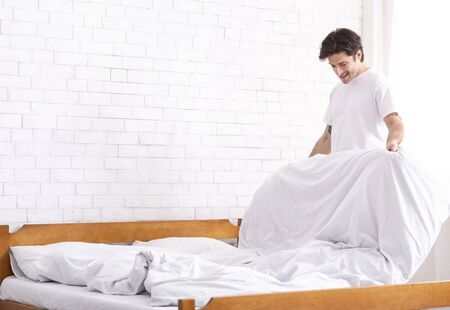 Foto de Living alone. Millennial guy making bed in morning, domestic chores concept, empty space - Imagen libre de derechos