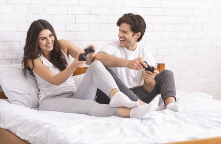 Weekend entertainment. Happy couple playing video games at home, sitting with joysticks on bed and laughing, free space