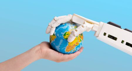 Future technology and artificial intelligence concept. Human and robot hands holding earth globe, blue background