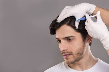 Photo pour Man with hair loss problem receiving injection in head, grey background, empty space - image libre de droit