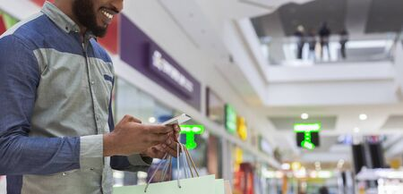 Photo pour Handsome african american guy typing funny text message on cellphone and smiling in shopping mall, panorama, copy space - image libre de droit