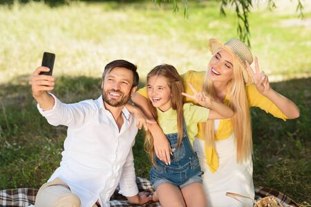 Photo for Cheerful family making selfie outdoors in park, having picnic at weekends - Royalty Free Image