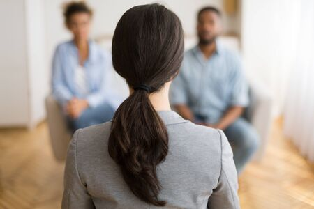 Photo pour Couples Therapy Session. Counselor Listening To Afro Husband And Wife Sharing Problems In Office. Back View, Selective Focus, Copy Space - image libre de droit