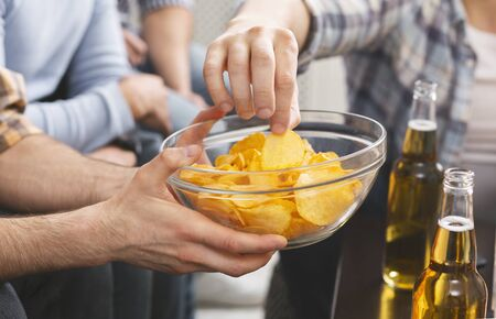 Photo pour Close up of man holding bowl with chips sharing with friends at home party - image libre de droit