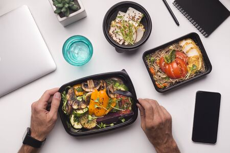 Photo for Online delivery. Man eating healthy food during lunch time in office, cellphone with blank screen - Royalty Free Image