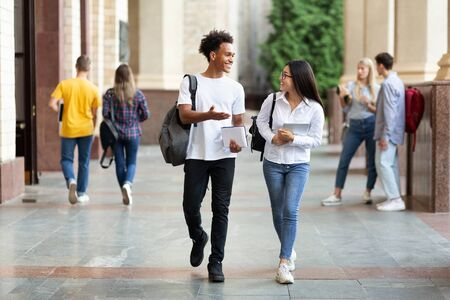 Photo for Happy diverse students walking in college campus during break and talking, copy space - Royalty Free Image