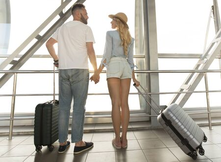 Photo for Traveling concept. Loving couple standing near window of international airport terminal, back view - Royalty Free Image