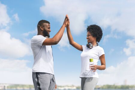Photo pour Couple Losing Weight Together. Fit Afro Man And Woman Giving High Five After Morning Jogging Near River. Panorama - image libre de droit
