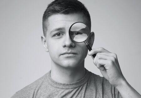 Photo pour Portrait of young man looking through magnifying glass, monochrome photo - image libre de droit