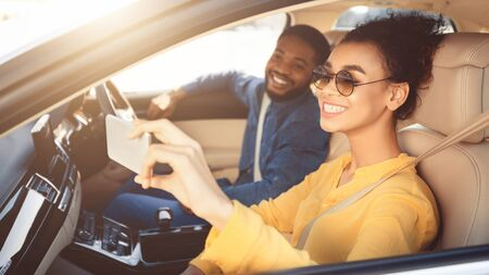 Photo for Happy african american couple taking selfie in car, driving to new destination, free space - Royalty Free Image
